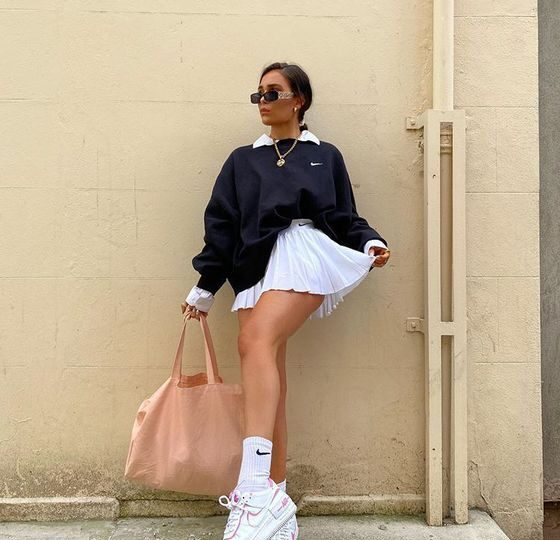 A girl wearing the latest fashion trends in a white tennis skirt for the fashion season.