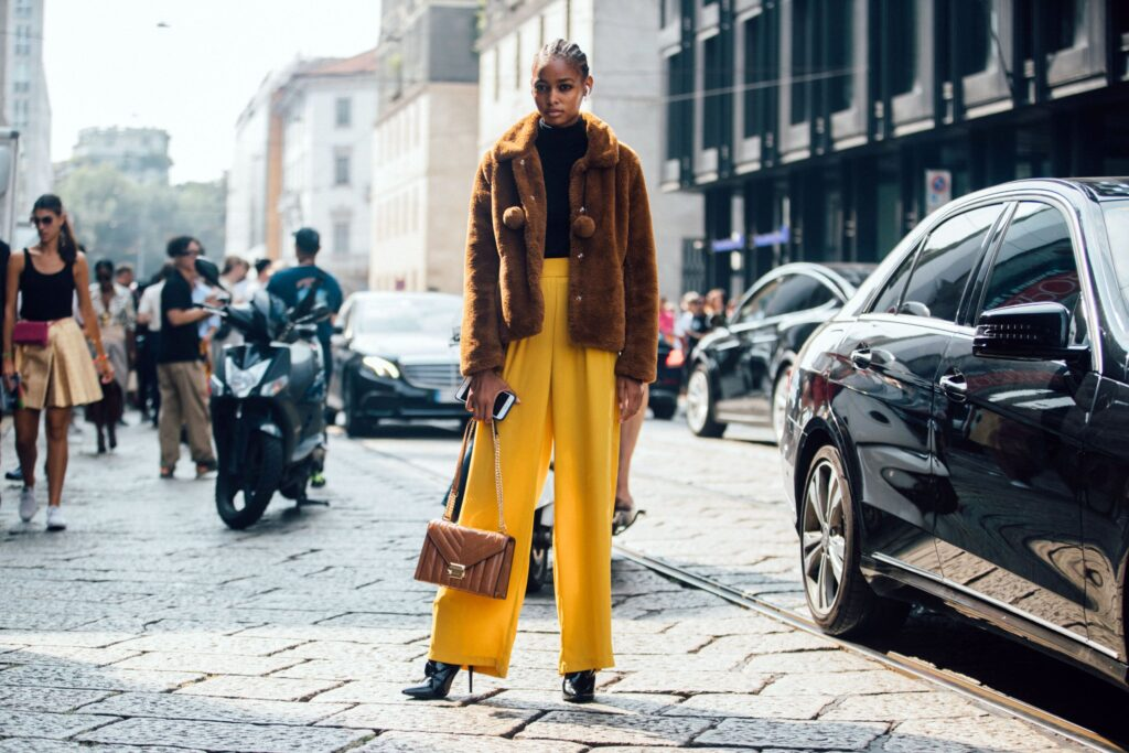 a girl getting photographed at new york fashion week and paris fashion week, a black girl standing in the middle of the street, a girl with a brown teaddy coat and some yellow wide leg trousers. the girl is wearing a winter outfit