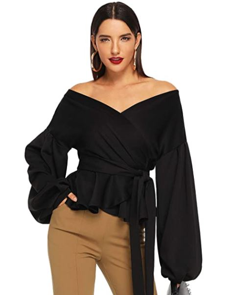 girl standing with her hair slicked back. a girl with red lipstick on. a girl with black off the shoulder top, a girl with tan pants on.