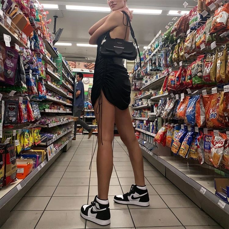 a girl standing in a gas station. a tall girl standing in the store. a girl with air jordan 1s on. a girl with a prada bag on. a girl with a dress and sneakers on.