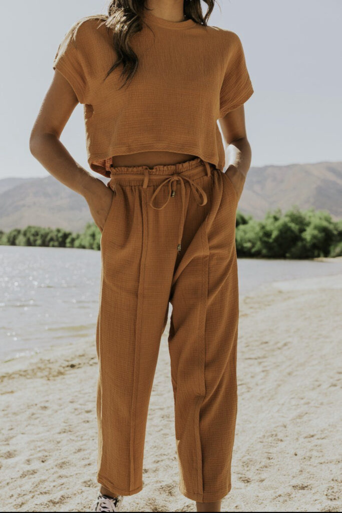 a girl standing on the mountain. a girl with some carmel or tan joggers on. a girl with her hands in her pocket.