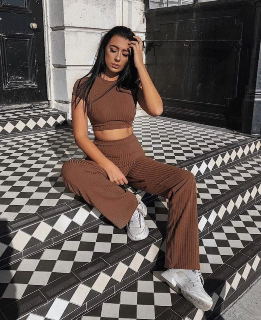 a girl sitting on stairs. a girl with a two piece set on. a girl with a boohoo outfit on. a girl with a crop top on. a girl with black hair. a girl taking a off guard picture.