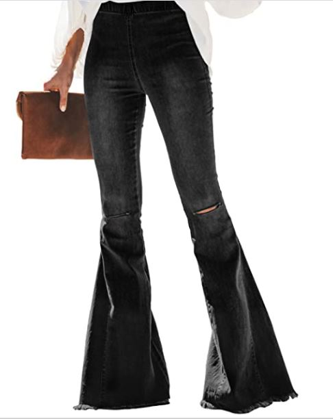 black wide leg pants on a women. a lady standing with her legs open. a girl holding a brown clutch. a girl with wide leg jeans and rips in the jeans.