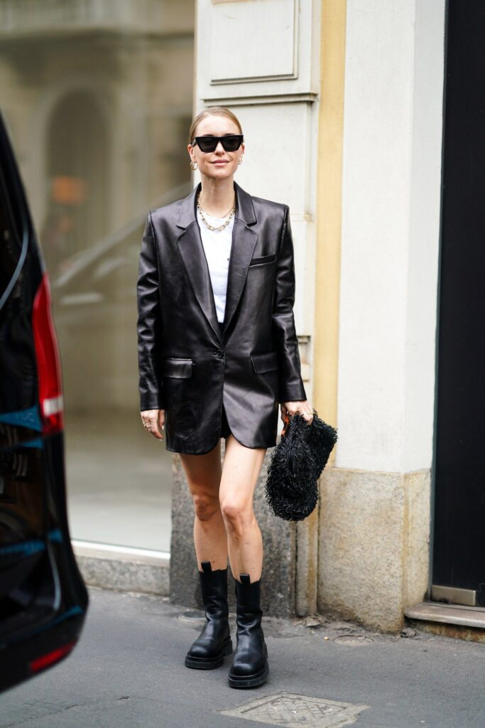 A girl walking on the street. a girl wearing black chunky boots and a black leather blazer. this girl paired her black leather blazer with some black sunglasses.
