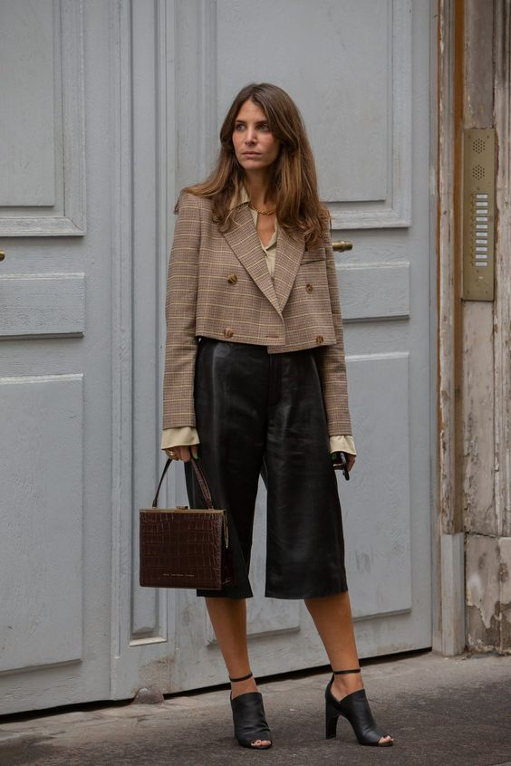 a girl standing in fron a building. a girl with leather shorts. a girl with a cropped blazer on. a girl following 2021 winter trends. a girl with a brown crocodile bag on. a girl in new york city. a girl in paris