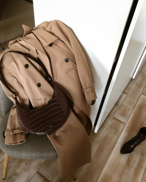 A tan trench coat laying on the chair. a jw pei handbag with a trench coat. paris fashion style. a white furnished house.