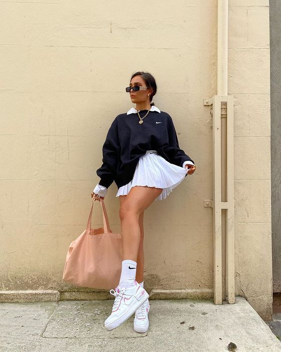 a girl standing outside posing in front of a camera. This girl has a tennis skirt outfit on. A girl with a oversized nike sweater with a white tennis skirt. A girl with Air Force 1's on and a oversized tote bag