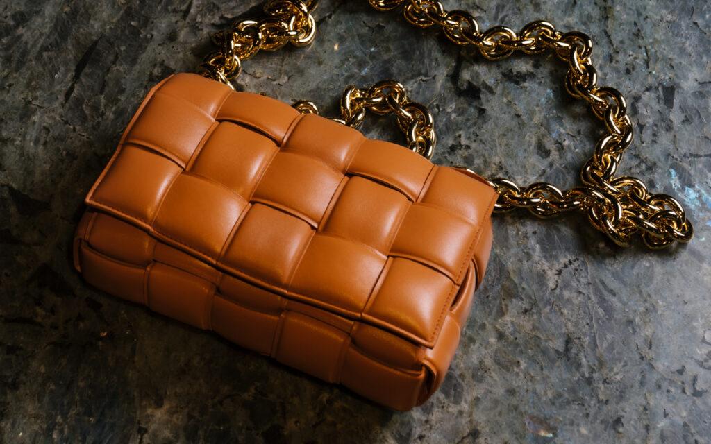 a quilted chain handbag. A bottega Veneta orange quilted handbag with a gold chain handle.