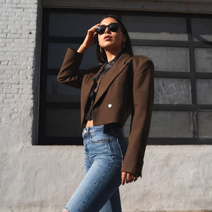 a girl standing in the middle of the street posing. a girl with some jeans on. a girl that has a winter outfit on. a girl with sunglasses on her face. a girl with a cropped blazer on.
