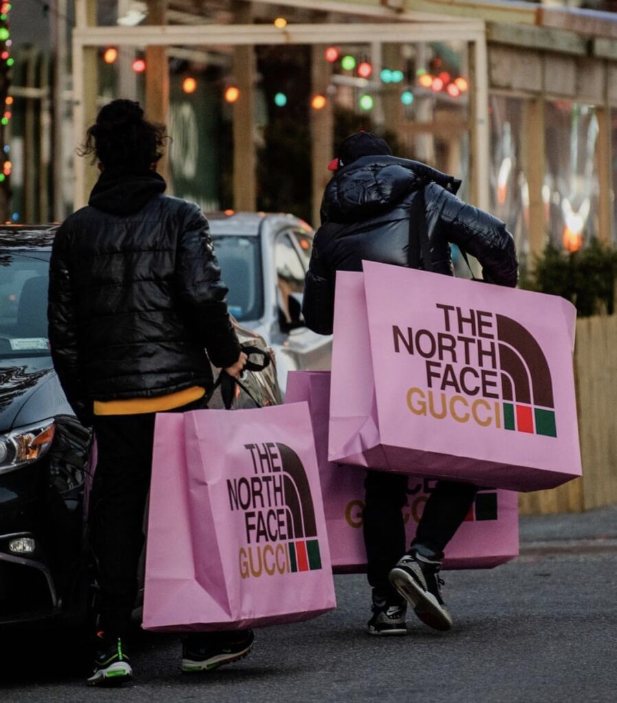 people with shopping bags. a person with shopping bags. Designer shopping bags from the store. people in the middle of the street. The North Face x Gucci shopping bags. People with the North Face x Gucci collection bags.