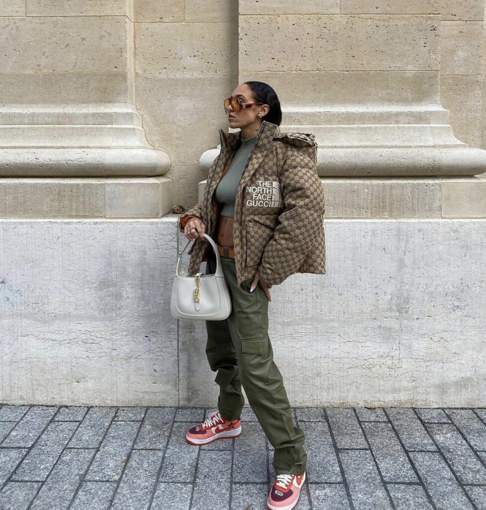 a girl standing in front of a building, a girl with The North Face x Gucci collection puffer coat on. a girl with some sneakers on. a girl with a white purse. a girl posing for a picture