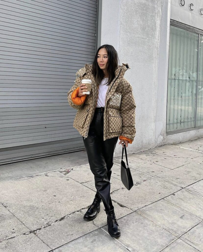 Aimee Song with The North Face x Gucci collection on. The North Face x Gucci collection puffer coat. a girl posing with a black purse. a girl wearing gucci in street style look.