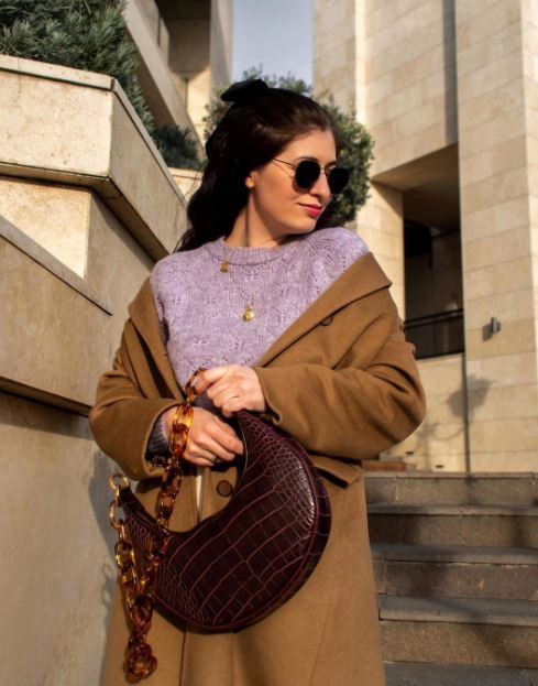 a girl standing outside. a girl wearing sunglasses. a girl with a purple shirt on. a girl with a ten trench coat on. a girl holding her purse. a girl with a jw pei handbag. a girl in front of stairs. a girl at golden hour. a street style fashion look.