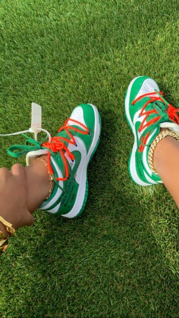a girl sitting down on the grass. a girl sitting in the park. a girl with off white nike dunks on. a girl with green shoes on.