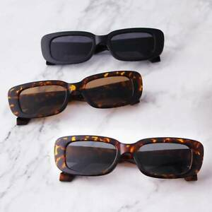 rectangle sunglasses on top of marble counter top. black rectangle sunglasses. Brown rectangle sunglasses for a winter outfit. a group of sunglasses on a table.