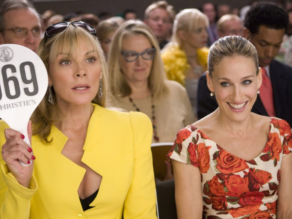two friends at a auction. a girl with a yellow suit on. sex and the city the movie. Samantha will not be returning to sex and the city reboot