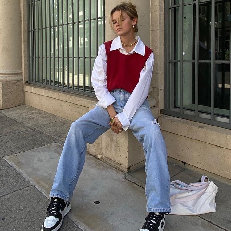 A girl sitting on a stoop. A girl with oversized jeans on. A girl with air Jordan 1s on. A girl with a red sweater vest on.