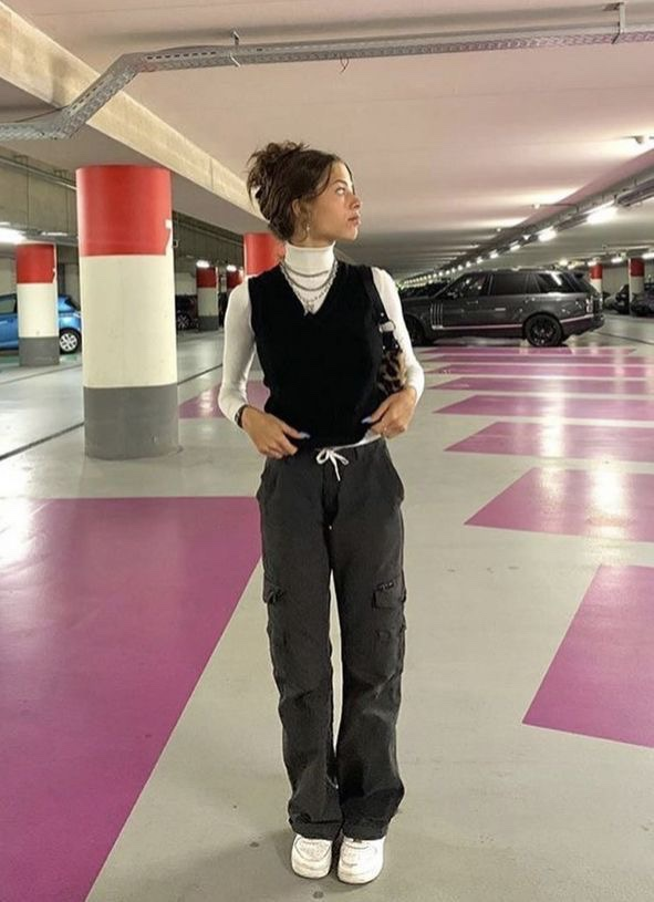 A girl standing in a parking garage taking pictures. A girl posing in a parking garage. A parking garage photoshoot inspiration. A girl styling a sweater vest