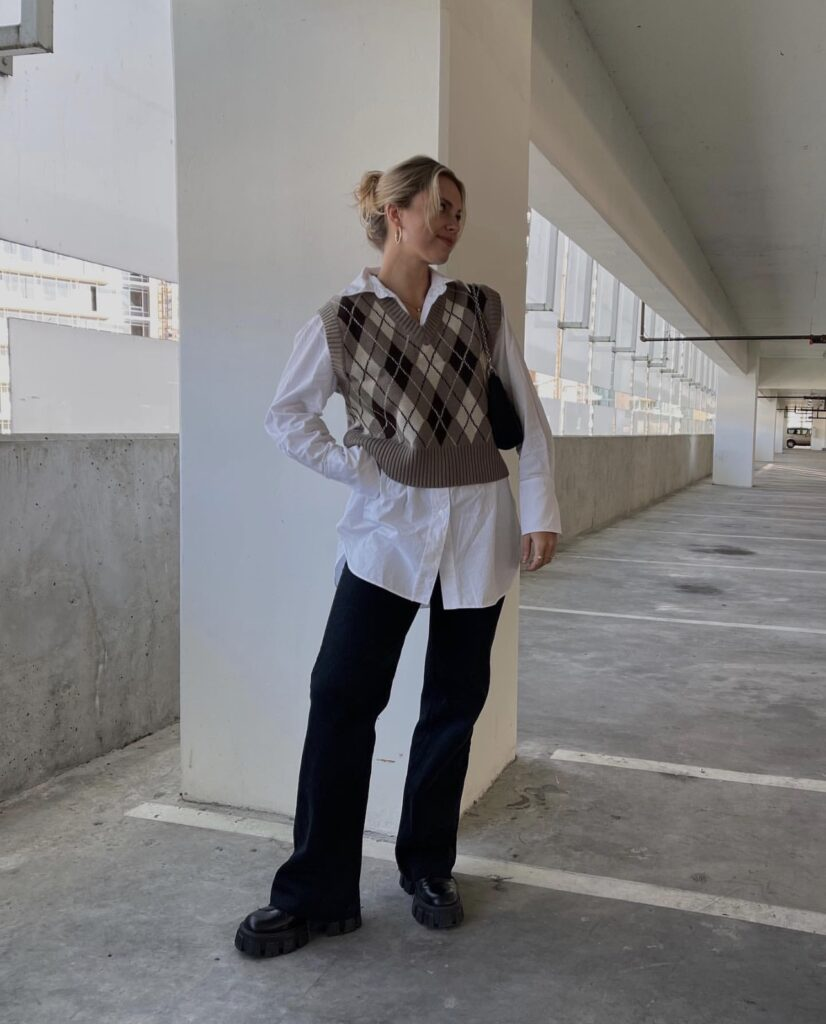A girl posing in a parking gag rage. A girl with a plaid print sweater vest on
