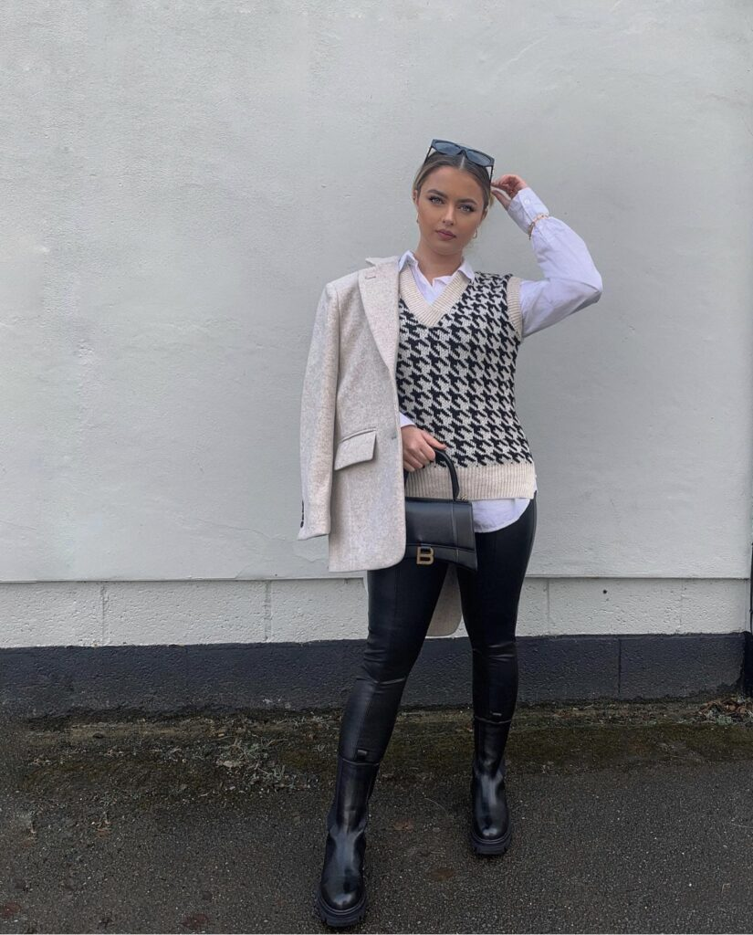 A girl posing in front of her building. A girl with a herringbone sweater vest. A girl with cowboy boots on. A girl with a black leather blazer. A balenciaga bag outfit