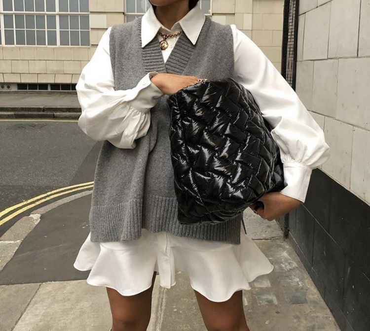 A girl standing in the street. A girl standing holding a big oversized bag. A girl with a sweater vest on