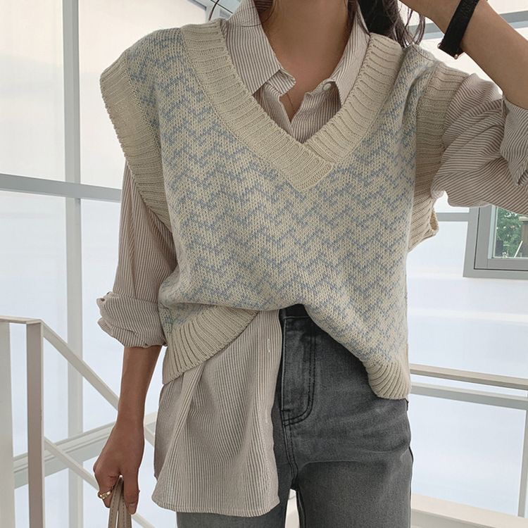 A girl standing posing. A girl with her sweater vest tucked in