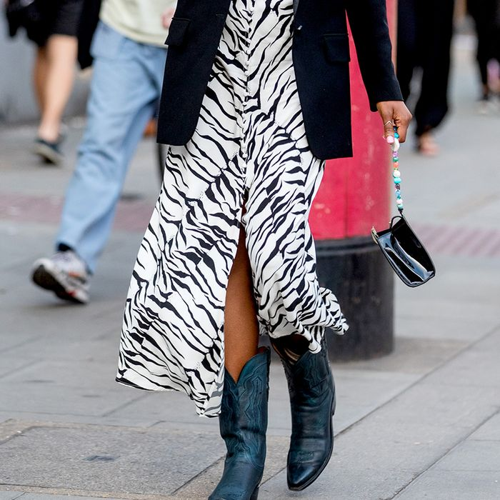 a girl standing and posing for the camera in zebra print . how to style zebra print for the perfect outfit inspo